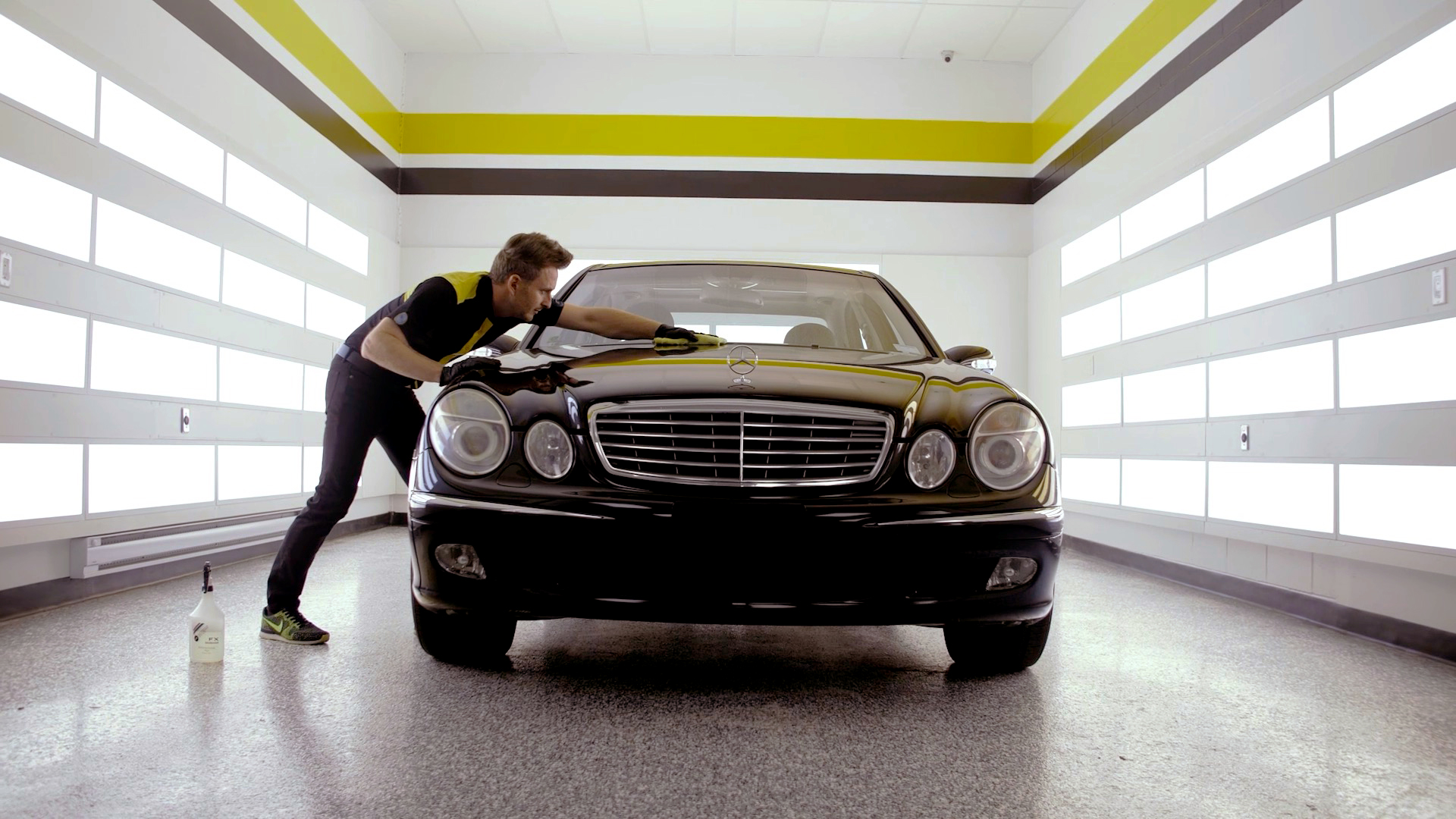 A RestorFX technician finishing the restoration of a shiny, brilliant black Mercedes lit with dramatic wall lights