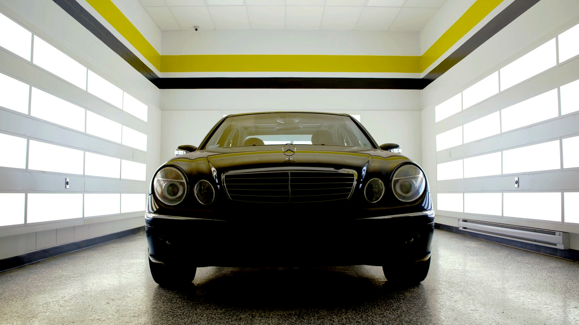 A black sedan in a RestorFX Center dramatically lit from both sides with yellow and black solid bands on high walls